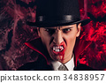 handsome man dressed in a Dracula costume for 34838957