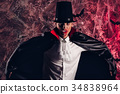 handsome man dressed in a Dracula costume for 34838964