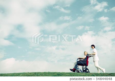 Nursing care nurse senior wheelchair blue sky 34844048