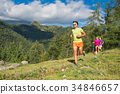Sporty man and young girls running together on the grass in a mo 34846657