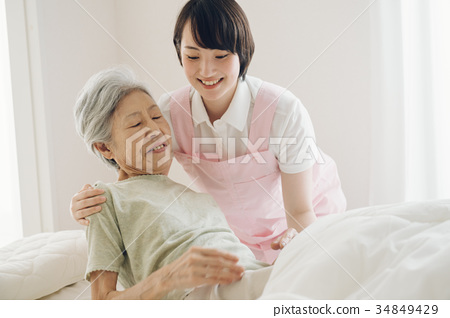 Care worker and senior visiting nursing home care 34849429