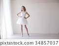 girl in a wedding dress stands in a white room 34857037