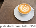 A white cup of coffee latte art on wood table 34858959