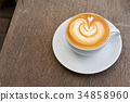 A white cup of coffee latte art on wood table 34858960