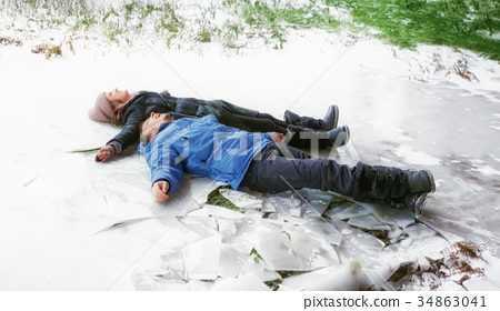 Young Man and Woman Lying On The Snow 34863041