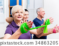 Physio showing senior couple how to use rubber 34863205