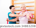 Physio assisting elderly woman during exercise 34863208