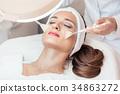 Beautiful woman during anti-aging facial massage 34863272