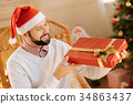 Happy man scrutinizing gift box in his hands 34863437