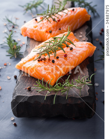 Raw salmon on wooden board with herbs 34887975