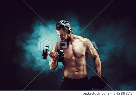 Man training muscles with dumbbells in studio on 34889873