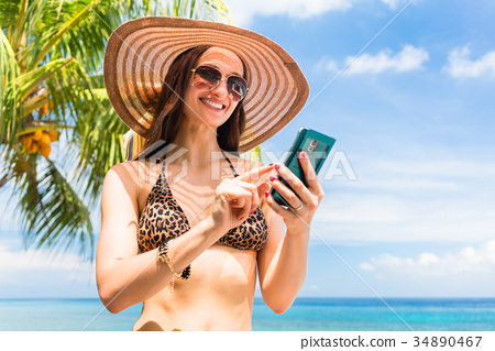 Tourist with smart phone on beach needs data 34890467