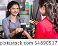 Female Customer paying for coffee with credit card 34890517