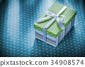 Gift box with ribbon on blue polka-dot tablecloth 34908574
