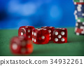 Red dice rotates on green felt, casino chips and 34932261