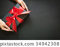 Gift box wrapped in black paper with red ribbon. 34942308