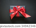 Gift box wrapped in black paper with red ribbon. 34942346