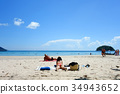 Woman Sunbathing on the Beach 34943652
