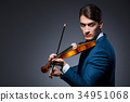 Young man playing violin in dark room 34951068