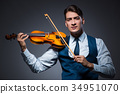 Young man playing violin in dark room 34951070