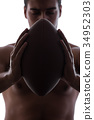 Ripped young man with american football isolated 34952303