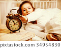 Woman in bed turning off alarm clock 34954830