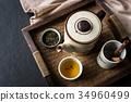 Tea set on wooden tray on black stone background 34960499