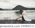 Lonely woman sitting on wooden pier 34960531