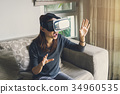 Young woman sitting on sofa and using vr headset 34960535