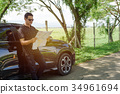 Muslim man lean car door and look into map  34961694