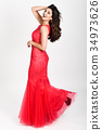 Young woman wearing long red dress on white background. 34973626