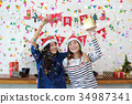 Two women in Santa hats and holding gift boxes 34987341