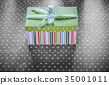 Present box on red tablecloth horizontal image 35001011