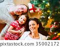 Young family lying under Christmas tree among 35002172