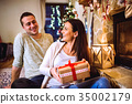 Couple in front of fireplace. Christmas time. 35002179