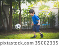 boy kicking football in the park 35002335