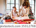 Senior couple in sweaters wrapping Christmas gifts 35012768