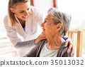 Health visitor and a senior woman during home 35013032