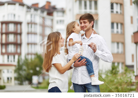 Happy family in front of new apartment building 35016721
