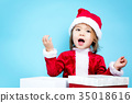 Happy toddler girl in a Santa costume 35018616