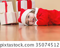 Little girl dressed in a santa claus hat and 35074512