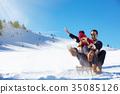 Young Couple Sledding And Enjoying On Sunny Winter 35085126