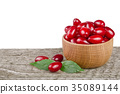 dogwood berry with leaf in bowl on wooden table 35089144