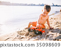 boy child playing makes splashes, beats hands on the water  35098609