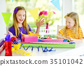Two cute sisters wrapping gifts in colorful wrapping paper 35101042