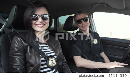 Two smiling police officers sitting in car 35114350