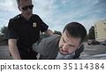 Policeman arresting criminal on parking lot 35114384
