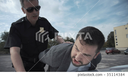 Policeman arresting criminal on parking lot 35114384