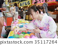 Young woman in yukata scooping yoyo at a festival 35117264