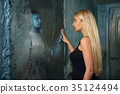 Frightened woman looking to the mirror  35124494